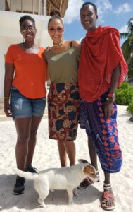 Asha standing wtih a Belgian woman and a Masai man in Zanzibar.